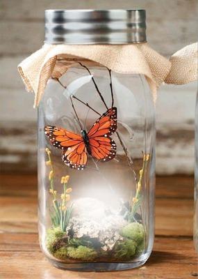 Botella con mariposa y flores